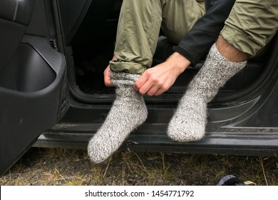 Adventurer, touirst or hiking affectionate changes shoes inside car after or before long wet walk in harsh conditions. Puts on pair or clean and dry wool socks to warm up feet in cold weather