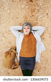 An adventurer young caucasian woman lying on grit ground beside a backpack wearing wool sweater and grey woolen cap with the orange as principal color