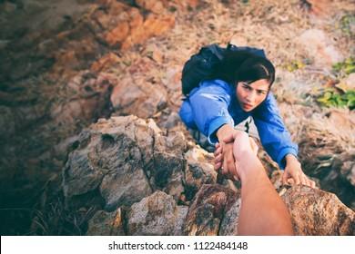 Adventurers helping asian woman to climbing the mountain.