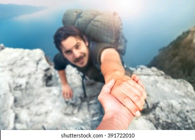 adventurers helping each other to climb the mountain
