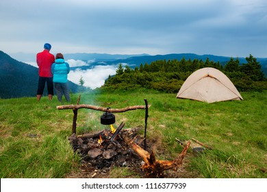 Adventurers relax in the camp next to the bonfire on a green meadow and admire the mountain ranges in the fog after the storm. Epic travel in the mountains. Back view.