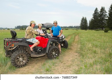 Adventures for adults - a trip on ATVs on not passable rural roads. Tourists on ATV in protective helmets from strikes and dirt, participate in the off-road race in the forest on a hot summer day.