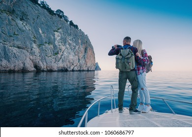 Adventures of a young couple on a yacht in the sea. Attractive man and woman backpackers travel by boat in the ocean near the mountains.