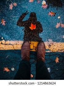 ADVENTURING THROUGH CANADA IN FALL/AUTUMN - Explorer/adventurer standing over puddle reflection on highway road, posing with red maple leaf in center of body. Traveller exploring Canada concept.