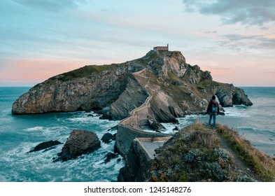 Adventurous adult boy exploring San Juan de Gaztelugatxe, Basque Country, Spain