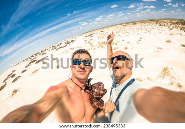 Adventurous best friends taking selfie at Etosha national park in Namibia - Adventure travel lifestyle enjoying moment and sharing happiness - Trip together around the world as alternative lifestyle