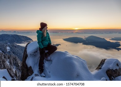 Adventurous Blond Caucasian Girl sitting on top of a snow covered mountain during a colorful winter sunset. Taken on St Mark's Summit, North of Vancouver, BC, Canada. - Shutterstock ID 1574704708
