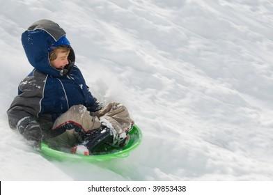 adventurous boy flies down snowy hill