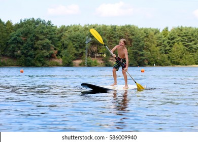Adventurous boy learning to paddle on stand up board. Happy child, teenage schoolboy, having fun enjoying adventurous experience on the river on a sunny day during summer holidays