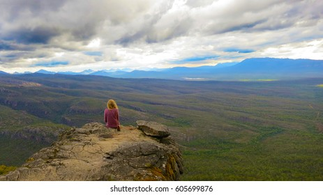 Adventurous and brave lonely Blonde curly haired girl enjoying the sights sitting off a cliff staring thinking into the huge foggy horizon of the Grampians National park, victoria, australia