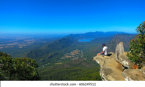 Adventurous brave young man sitting on a high cliff edge rock at the top of the Boroka Lookout view at the The Grampians National Park (Gariwerd), Victoria, Australia