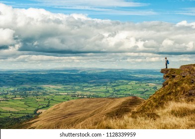 An adventurous child looking out on breathtaking scenery in the Brecon Beacons National park. Pen y Fan, Wales. United Kingdom, UK.