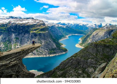 Adventurous couple at Trolltunga. Trolltunga (Troll tongue) is a piece of rock jutting horizontally out of a mountain in Odda in Hordaland, Norway.