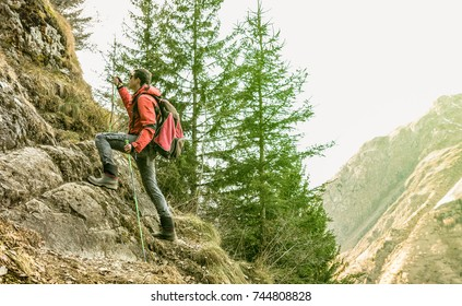Adventurous explorer trekking and climbing on french alps - Hiker with backpack and sticks walking on mountain - Hiking travel concept with sporty guy at excursion in wild nature - Greenery filter