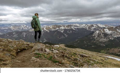 Adventurous female hiker on the Mt Yale Colorado 14er route overlooking the Rocky Mountains in the Sawatch Range.