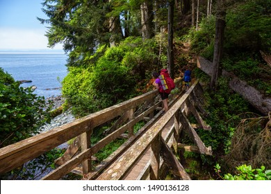 Adventurous female is hiking Juan de Fuca Trail on the Pacific Ocean Coast during a sunny summer day. Taken near Port Renfrew, Vancouver Island, BC, Canada.