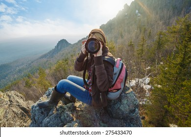 Adventurous female photographer sitting on the rock while photographing mountains facing the camera against setting sun. Wide angle perspective. Tourism, adventure, hiking concept.