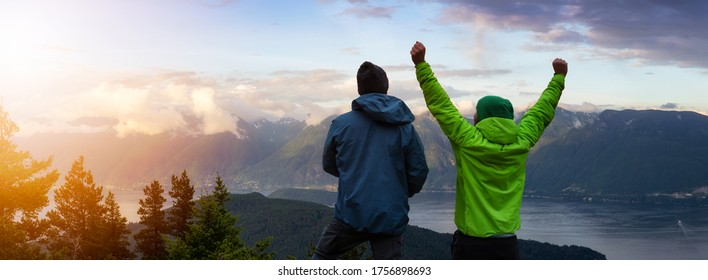 Adventurous Friends on top of a Mountain Top with Hands up. Sunset or Sunrise Composite. Background from Bowen Island, British Columbia, Canada.