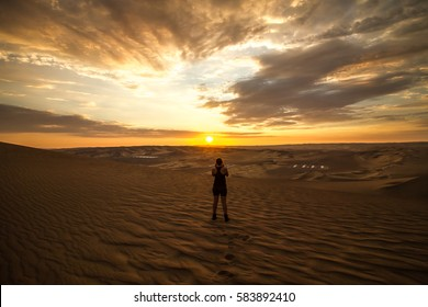 The adventurous girl contemplating the amazing colorful sky at sunset in Huacachina, Ica, Peru.