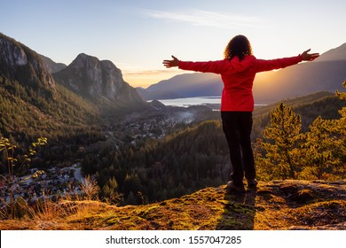 Adventurous Girl Hiking in the mountains during a sunny Autumn Sunset. Taken Squamish, North of Vancouver, British Columbia, Canada. Concept: Adventure, freedom, lifestyle