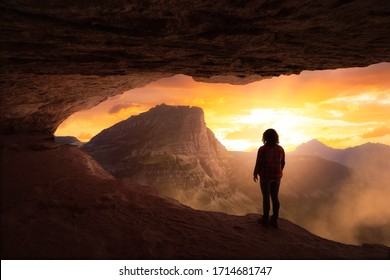 Adventurous Girl Looking out at a dramatic American Mountain Landscape from a rocky cave during a colorful sunset. Fantasy Adventure Composite.