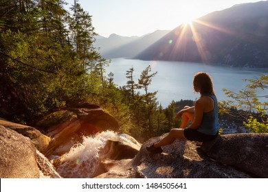 Adventurous Girl is sitting on top of a Beautiful Waterfall, Shannon Falls, and watching the sunset. Taken near Squamish, North of Vancouver, British Columbia, Canada.