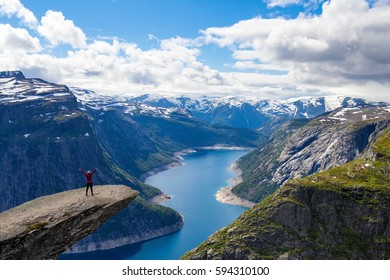 Adventurous girl at Trolltunga. Trolltunga (Troll tongue) is a piece of rock jutting horizontally out of a mountain in Odda in Hordaland, Norway.