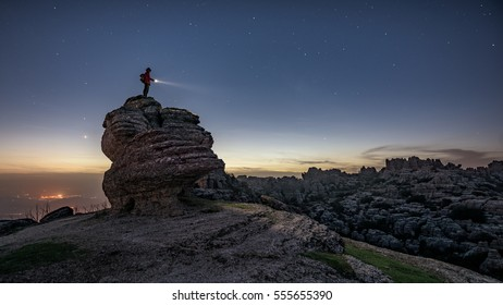 An adventurous hiker stands on top of a large lime stone rock in Torcal de Antequera, Spain, just after sunset.
