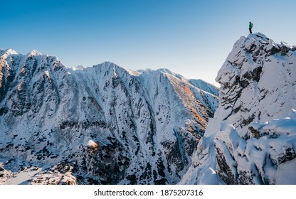 Adventurous man hiker on top of a steep rocky cliff overlooking winter alpine like moutain landscape of High Tatras, Slovakia. Alpine mountain landscape covered with glaciers, snow and ice.