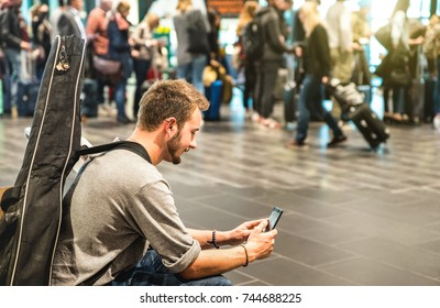 Adventurous man at international airport using mobile smart phone - Wanderer person at terminal gate waiting for airplane - Wanderlust travel trip concept with guy and guitar backpack - Focus on face
