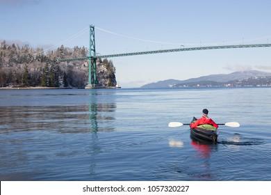 Adventurous man kayaking on an inflatable kayak near Lions Gate Bridge. Taken in North Vancouver, British Columbia, Canada.