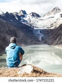 Adventurous man looking out mountain peak near of the Grimselsee, a glacial lake. The mountain passes in the Alps are a paradise for hiking