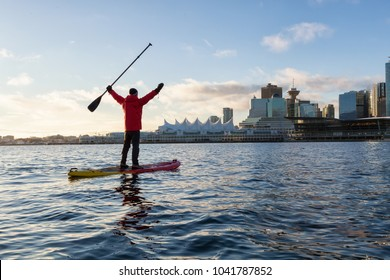 Adventurous man is paddle boarding near Downtown City during a vibrant winter sunrise. Taken in Coal Harbour, Vancouver, British Columbia, Canada.