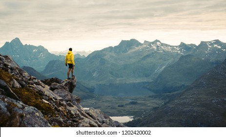 Photo of  Adventurous man is standing on top of the mountain and enjoying the beautiful view during a vibrant sunset. Beautiful Nature Norway natural landscape aerial photography