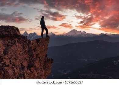Adventurous man is standing on top of the mountain and enjoying the beautiful view. Taken on top of Cheam Peak in Chilliwack, East of Vancouver, BC, Canada. Colorful Sunset Sky Art Render