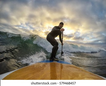 Adventurous Man Surfing the waves at the Pacific Ocean in Tofino, Vancouver Island, British Columbia (BC), Canada, during a cloudy winter sunset.