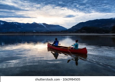 Adventurous people on a wooden canoe are enjoying the beautiful Canadian Mountain Landscape during a vibrant sunset. Taken in Harrison River, East of Vancouver, British Columbia, Canada.