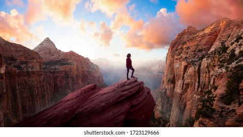Adventurous Woman at the edge of a cliff is looking at a beautiful landscape view in the Canyon during a vibrant sunset. Taken in Zion National Park, Utah, United States. Sky Composite Panorama