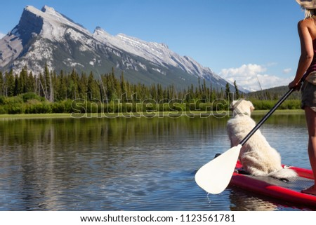 Adventurous woman on a paddle board with her dog is enjoying the beautiful sunny summer day on the lake. Taken in Banff, Alberta, Canada.