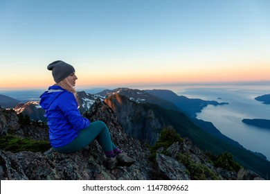 Adventurous woman on top of a mountain cliff is enjoying the beautiful summer sunrise. Taken on Mount Brunswick, Lions Bay, North of Vancouver, BC, Canada.
