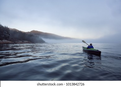 Adventurous woman is sea kayaking on an inflatable kayak during a vibrant winter sunset. Taken in Horseshoe Bay, West Vancouver, BC, Canada. Concept: adventure, holiday, vacation, explore