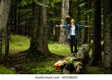 adventurous woman travels through the forest, standing with open hands and feeling the nature all around