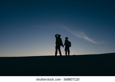 An adventurous young couple holding hands, silhouetted against the sunset, at the peak of a hill or dune.