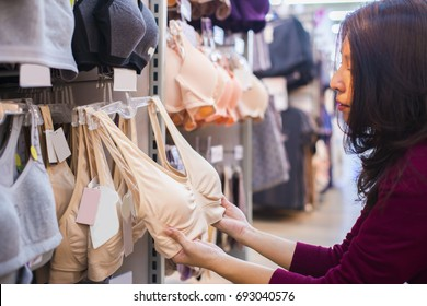 Advertise, Sale, Fashion concept - Asian woman standing in supermarket, looking through hangers with lingerie, choosing new underwear in shop.