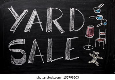 An advertisement or announcement of a Yard Sale on a used blackboard. Yard sales are a traditional way to make money and clear out unwanted or old belongings from your home.