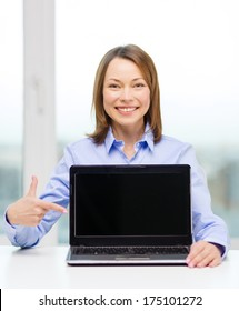 advertisement, business and technology concept - smiling businesswoman pointing finger to blank black laptop screen