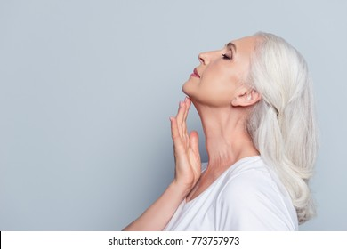 Advertisement concept. Close up profile with copy space of nice, charming, aged woman, touching her skin of neck with hand over grey background