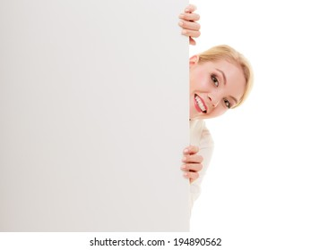 Advertisement. Funny woman hiding behind blank copy space banner isolated on white. Businesswoman recommending your product