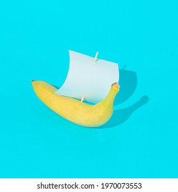 Advertisement idea with a yellow banana like a ship with a shadow and a sail of paper against pastel blue background. Minimal summer nature concept.