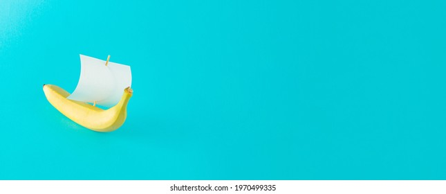 Advertisement idea with a yellow banana like a ship and a sail of paper against pastel blue background. Minimal summer nature concept in horizontal orientation.